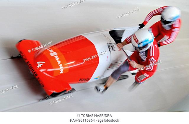 Swiss bobbers Fabienne Meyer (L) and her brakewoman Michelle Huwiler start a run at the women's two-person bobsleigh world cup at the artificial ice track at...