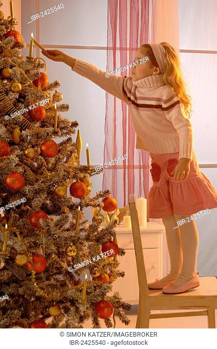 Girl lighting a candle on a festively decorated Christmas tree