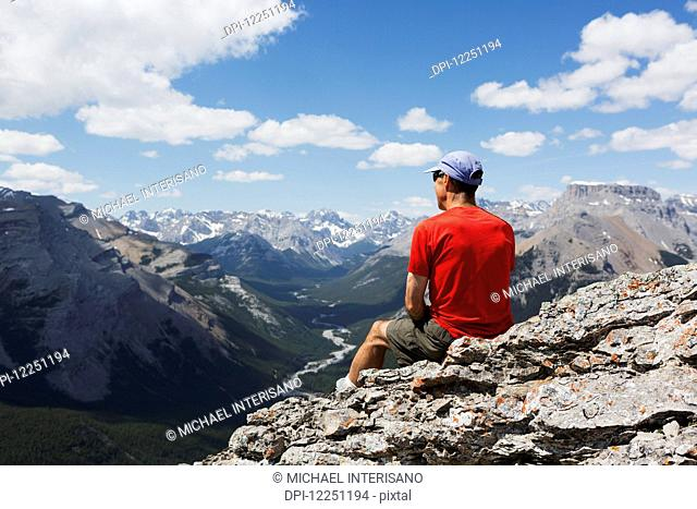 Male hiker sitting on a rocky cliff ledge overlooking a river valley below with mountain range in the distance with blue sky and clouds; Alberta, Canada