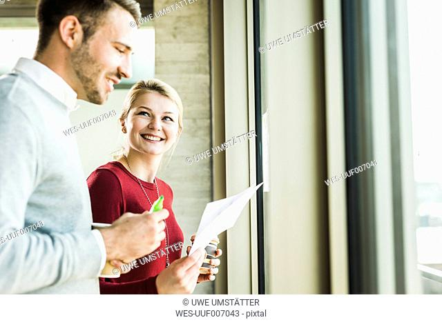 Two smiling colleagues with paper at office window