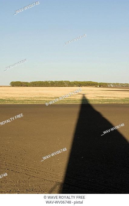 Long shadow of wind turbine on ground