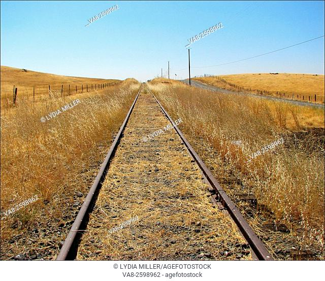 These endless railroad tracks march across golden hills located in Folsom, California