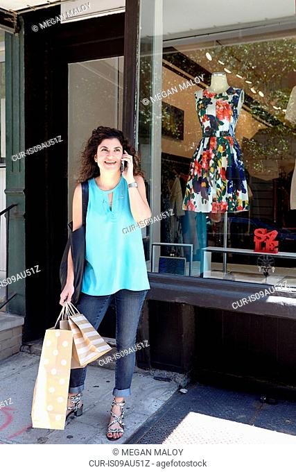 Mature woman exiting fashion boutique carrying shopping bags, using smartphone