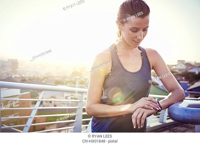 Female runner resting checking smart watch fitness tracker on sunny urban footbridge