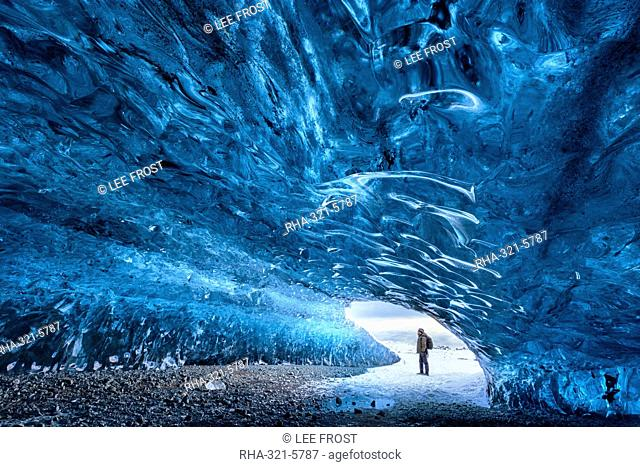 View from inside ice cave under the Vatnajokull Glacier with person for scale, near Jokulsarlon Lagoon, South Iceland, Polar Regions