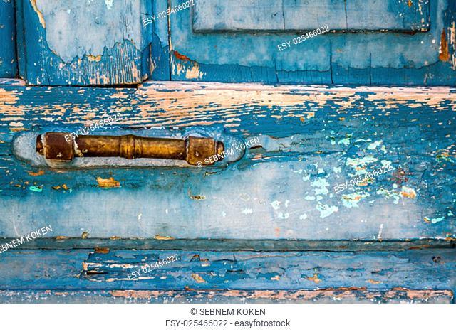 Yellow door handle of traditional old wooden blue door