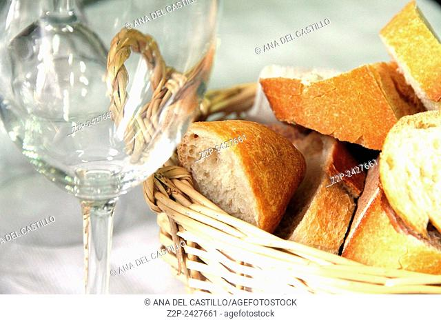 Empty glass and fresh crusty bread in a basket