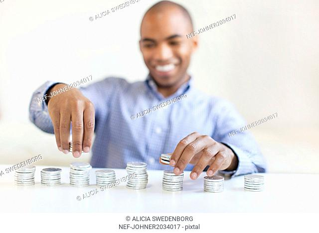 Young man stacking coins