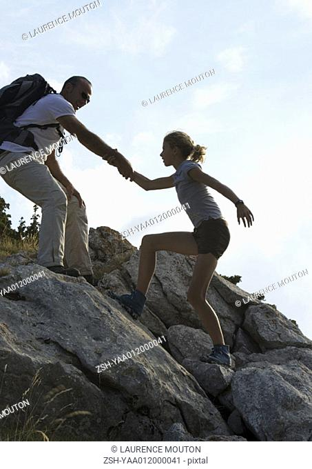 Hikers, man helping girl up rocks