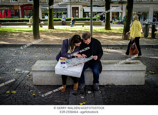 Two people sit and study a map in the precepts of Rouen Cathedral, Normandy, France