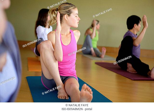 Mixed yoga group doing class in exercise studio