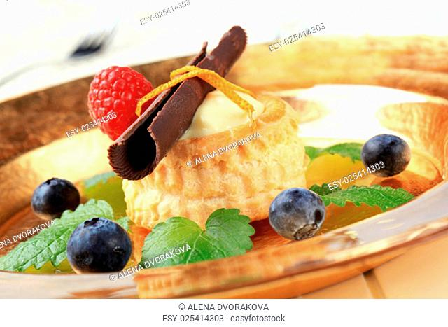 Cream filled vol-au-vent garnished with chocolate curl and fruit