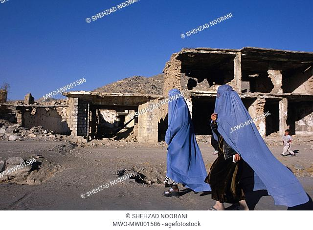 Two Afghan women covered in typical blue coloured Afghani burqa, passes by heavily damaged buildings caused to series of wars and fraction fighting that...