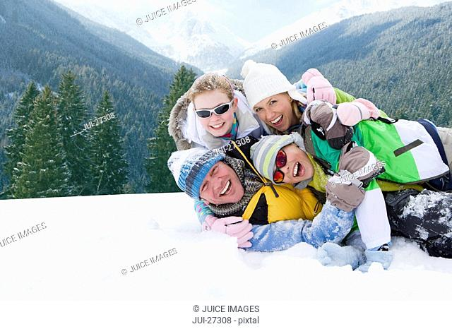 Family laying and hugging in snow