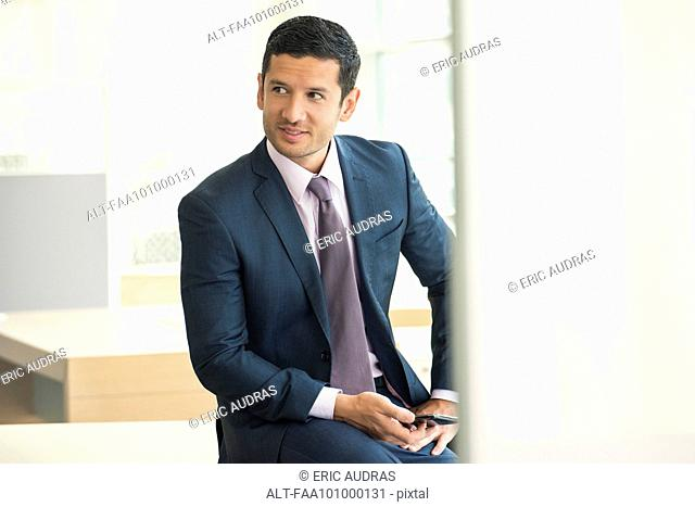 Businessman sitting with smartphone in hand, looking away and smiling