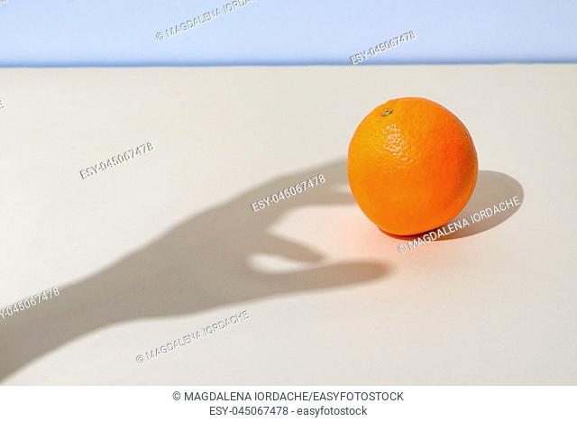 Concept of Male hand picks up an orange