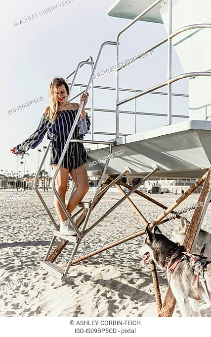 Young woman with pet dogs by lifeguard tower