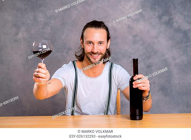 young man sitting at the table and drinking red wine