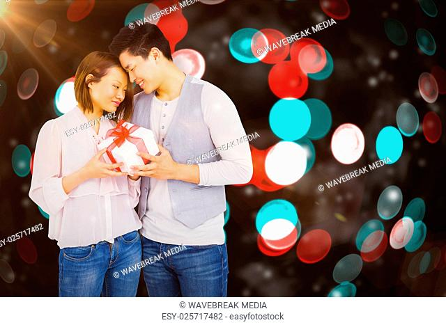 Composite image of young man giving present to woman