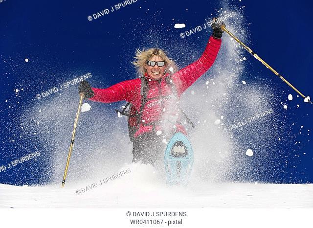 A woman snowshoeing in deep fresh powder and having fun