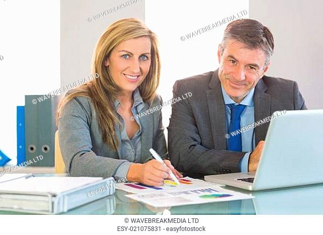 Two concentrated business people smiling at camera trying to understand figures