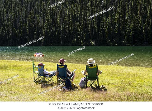 Three people relax by Lightning Lake in E. C. Manning Provincial Park, British Columbia, Canada