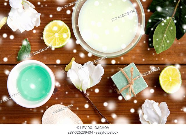 beauty, spa, body care and natural cosmetics concept - bowls with citrus body lotion, cream and handmade soap bar on wooden table over snow