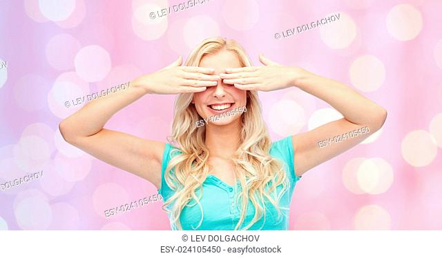 emotions, expressions and people concept - smiling young woman or teenage girl covering her eyes with palms over pink holidays lights background
