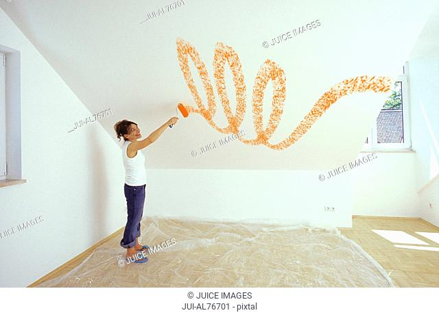 Portrait of a young woman painting a design on her blank wall