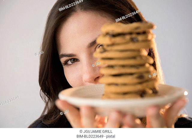 Caucasian woman showing pile of cookies on plate