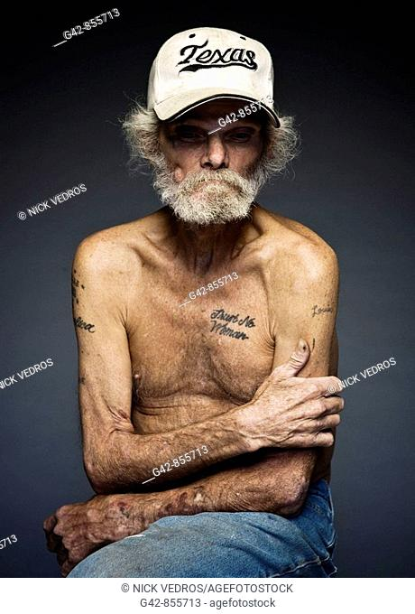 Portrait of man displaying a tattoo that says 'Trust No Woman'
