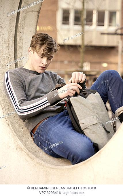 young model man opening his bag, in Hamburg, Germany
