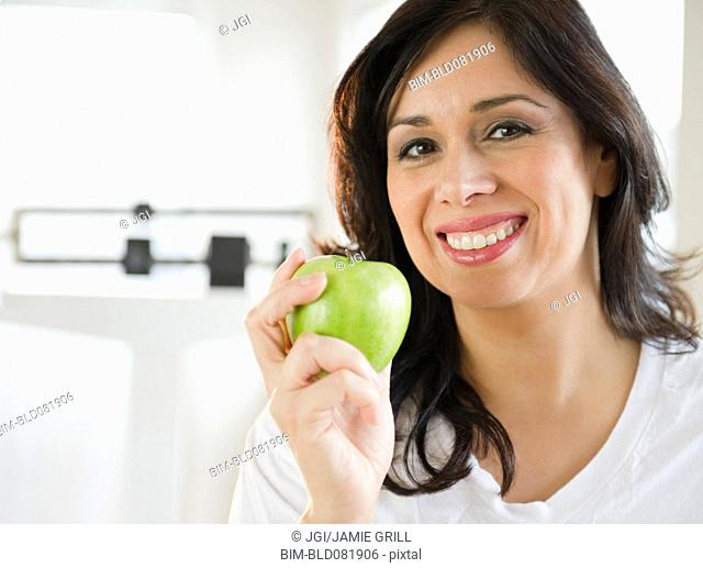 Smiling Hispanic woman holding a green apple