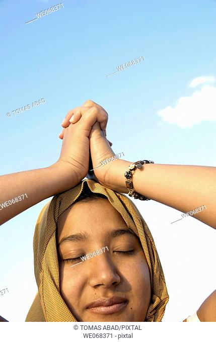 Woman praying wearing a 'hijab' (a veil - from the Arabic word 'hajaba'- to cover)