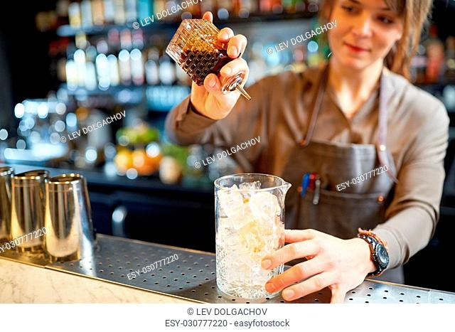 alcohol drinks, people and luxury concept - woman bartender with glass of ice and syrup preparing cocktail at bar