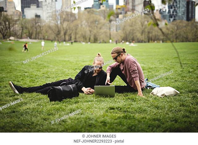 Men using laptop in park