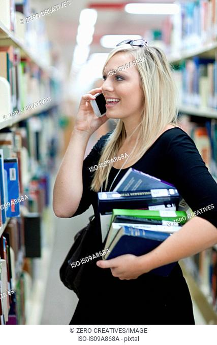 Female student on smartphone holding pile of books