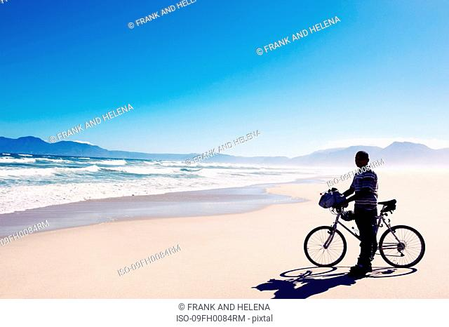 Black man with bike standing on beach
