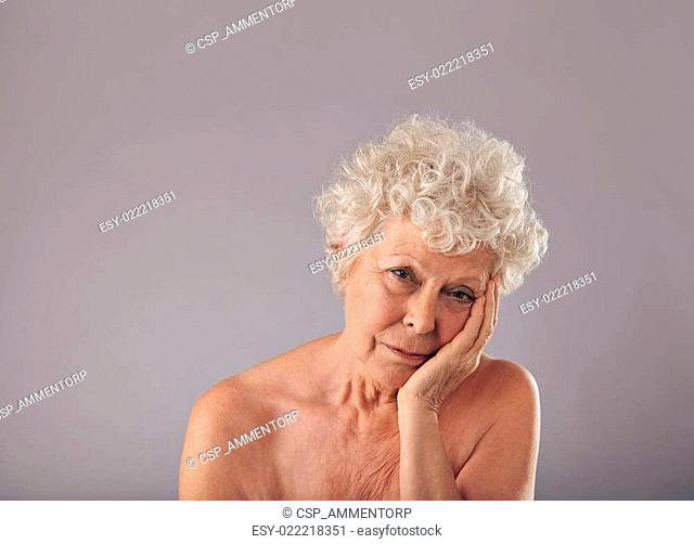 Upset senior woman on grey background