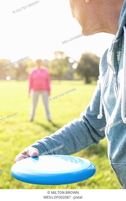 Senior couple playing frisbee in a park