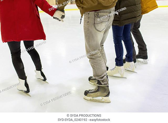 close up of friends on skating rink