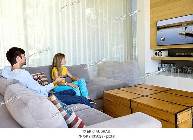 Father watching television with his daughter