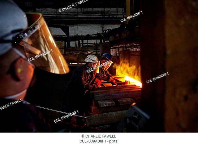 100mm square steel billet is removed from furnace as cold steel billet waits to be heated, with furnace door operator in foreground