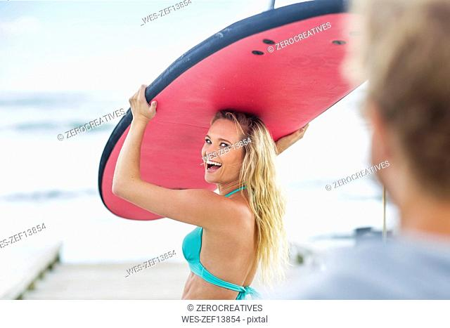 Happy woman carrying surfboard