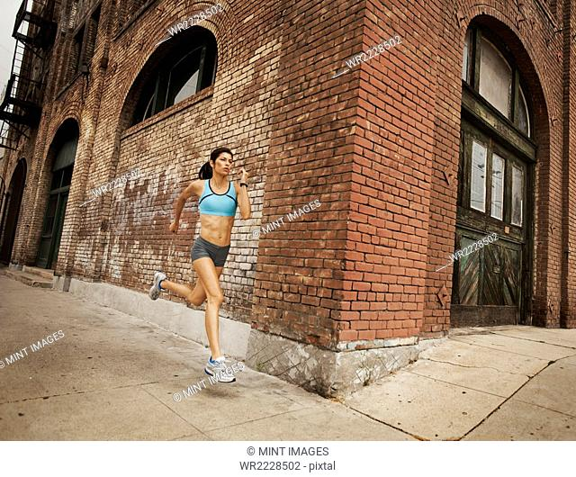 A woman running along an urban road, jogging, stretching her arms and legs