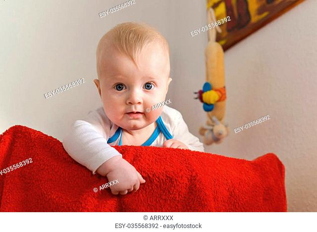 Portrait of a six month old baby boy looking curious at the camera