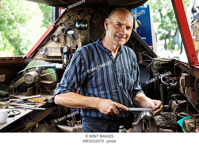 Blacksmith standing on a narrowboat barge in his workshop, holding a metal file