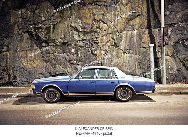 A blue car against a stone wall, Sweden