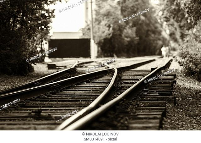 Horizontal black and white sepia railroad track bokeh with people background