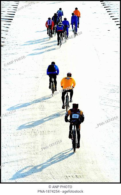 Mountain bikers over a frozen beach near Egmond aan Zee